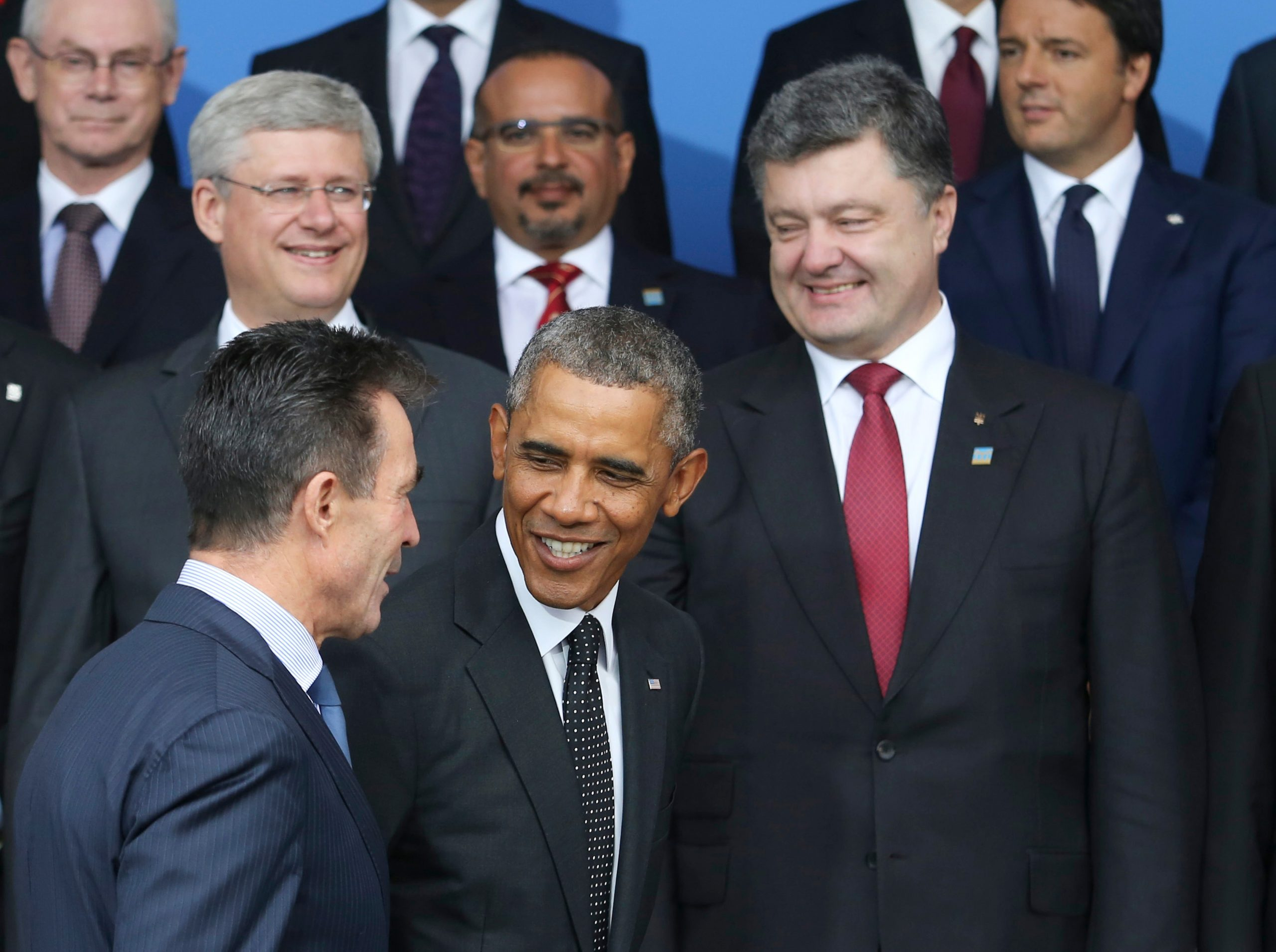 Barack Obama, centre, speaks with Anders Fogh Rasmussen, secretary general of the North Atlantic Treaty Organization (NATO), left, as Petro Poroshenko, billionaire and Ukraine's president, right, looks on before the family photograph at the NATO summit in Newport, U.K., on Thursday, Sept. 4, 2014.
