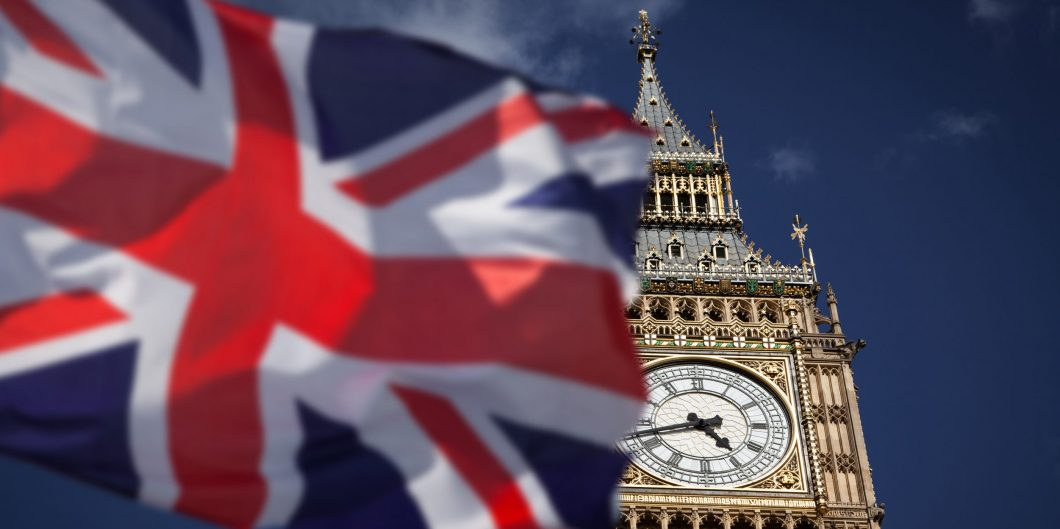 British union jack flag and Big Ben Clock Tower at city of westminster in the background – UK votes to leave the EU