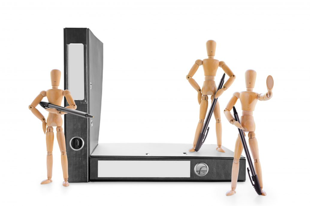 Three armed with pens wooden mannequins guarding office folders. Information security, legal protection or bureaucratic barriers concept