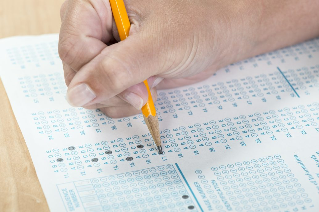 Student bubbling in answers on a standardized test form with a shallow depth of field