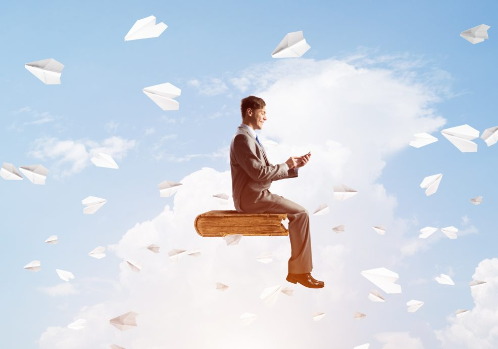 Businessman or student on book and paper planes flying around