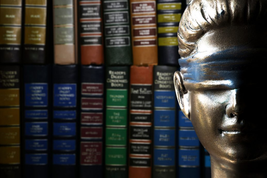 Face of Lady Justice (Symbol of Justice) with stack of legal text books