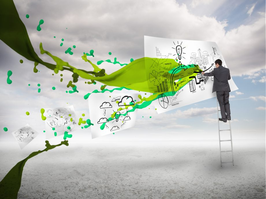 Businessman drawing on a paper next to green paint splash with blue sky on the background
