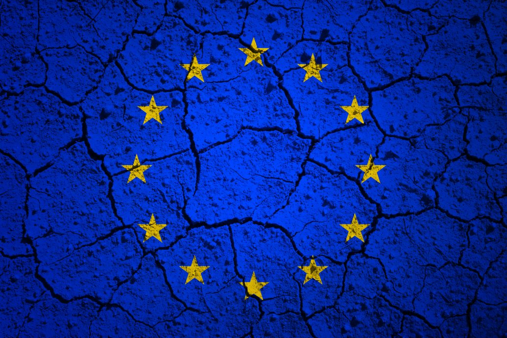European union flag painted on dry cracked soil texture background.