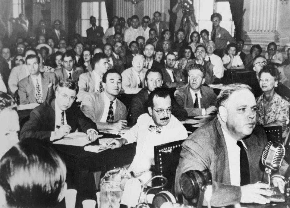 Whittaker Chambers before the House Un-American Activities Committee, Aug. 25, 1948. He repeated his testimony that State Department Director, Alger Hiss, was a secret communist. Hiss is in mid-ground left, looking into camera. (BSLOC_2014_13_57)