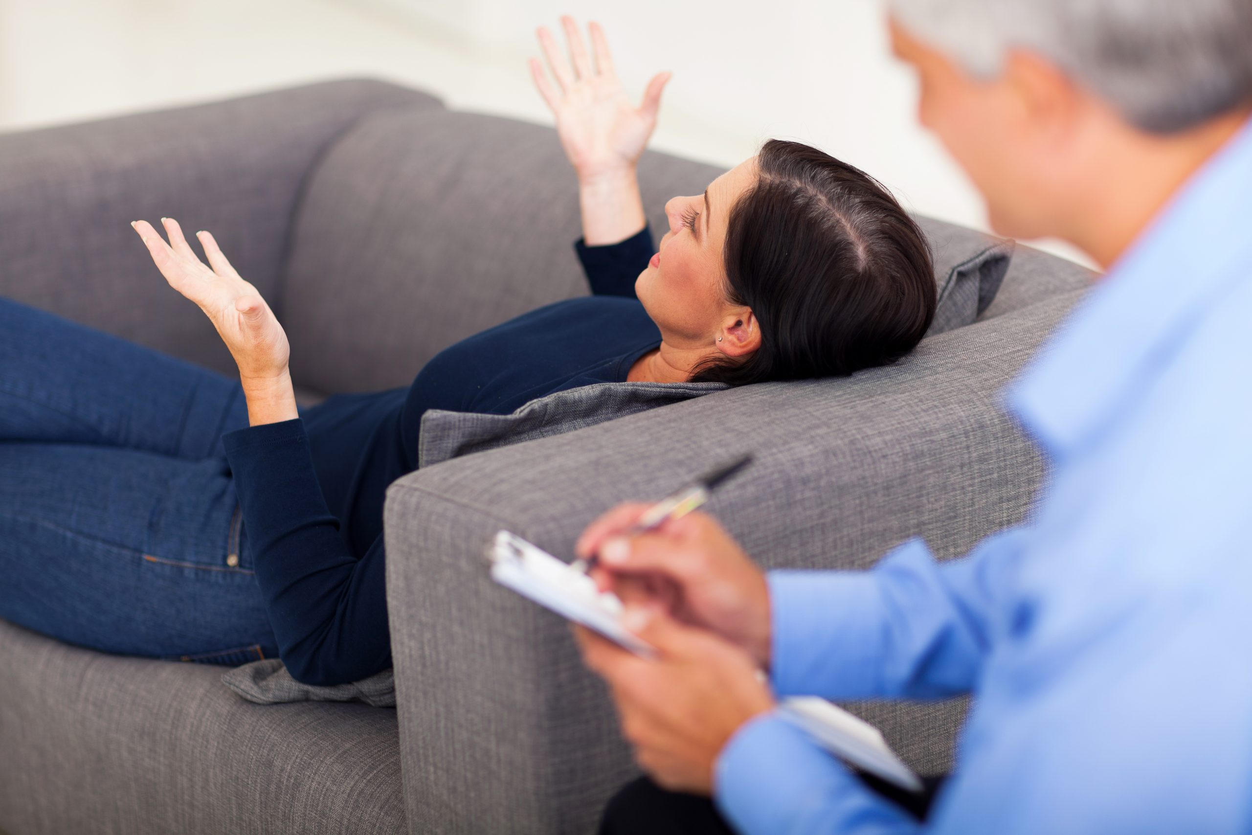 middle aged woman lying on sofa and talking to her psychologist