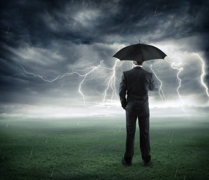 risk and crisis – businessman below storm with umbrella