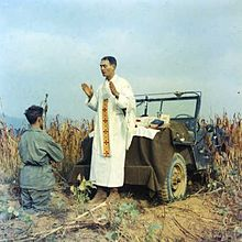 Father Emil Kapaun celebrating Mass using the hood of a Jeep as his altar, Oct 7, 1950.