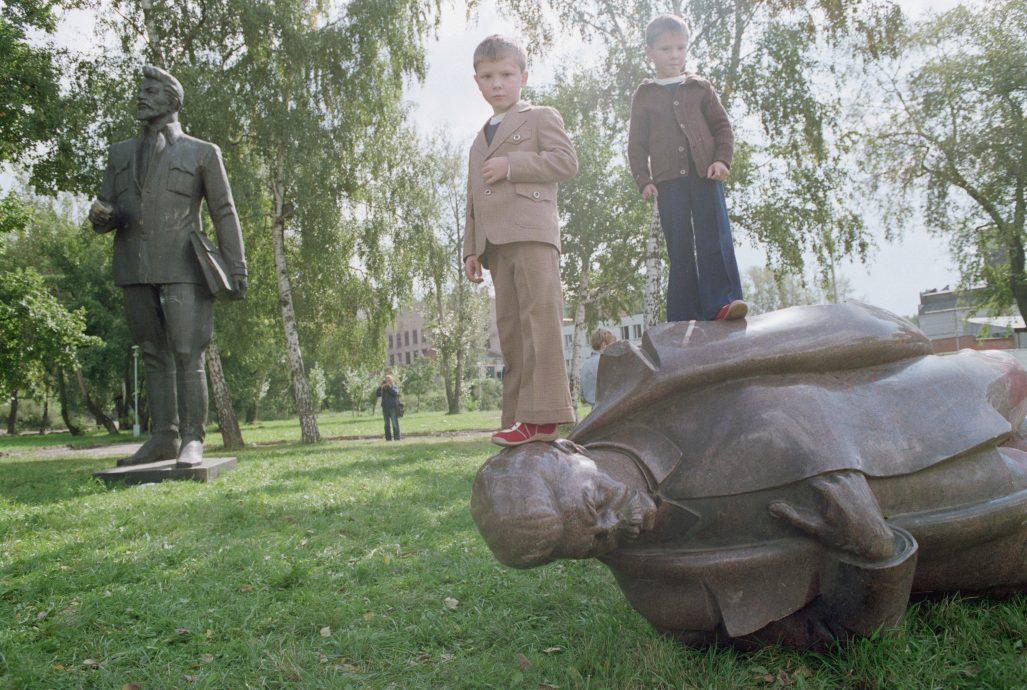 Children Standing on a Fallen Statue of Stalin