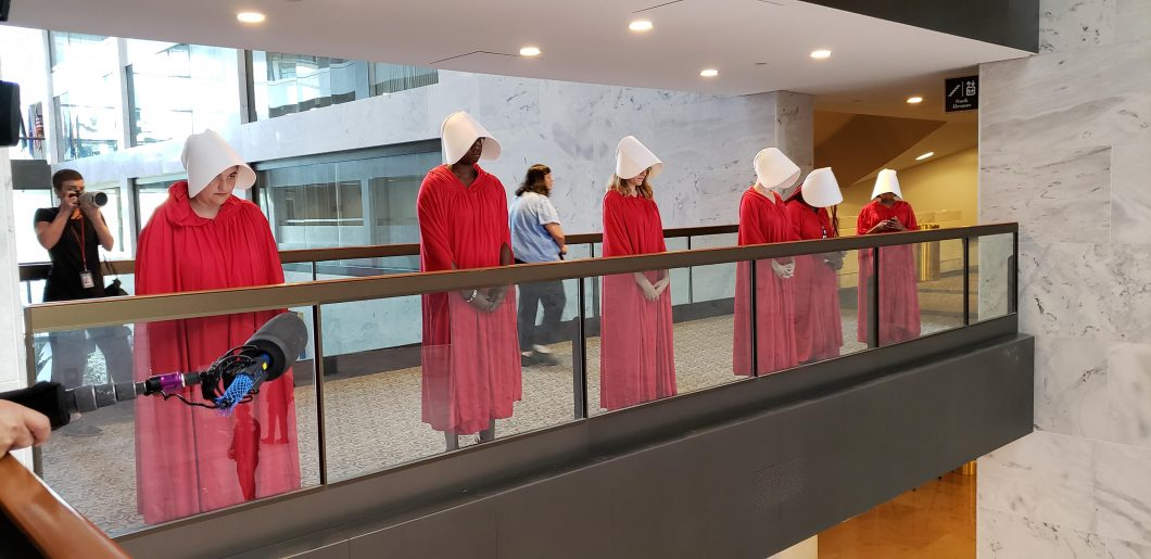 "Washington DC, September 3, 2018, USA: Protestors dressed as ""Hand Maidens"" line the hallway near the Judge Brett Kavanaugh nomination hearing to become the next Associate Supreme Court Justice. The protestors are concerned that Kavanaugh may try and over"