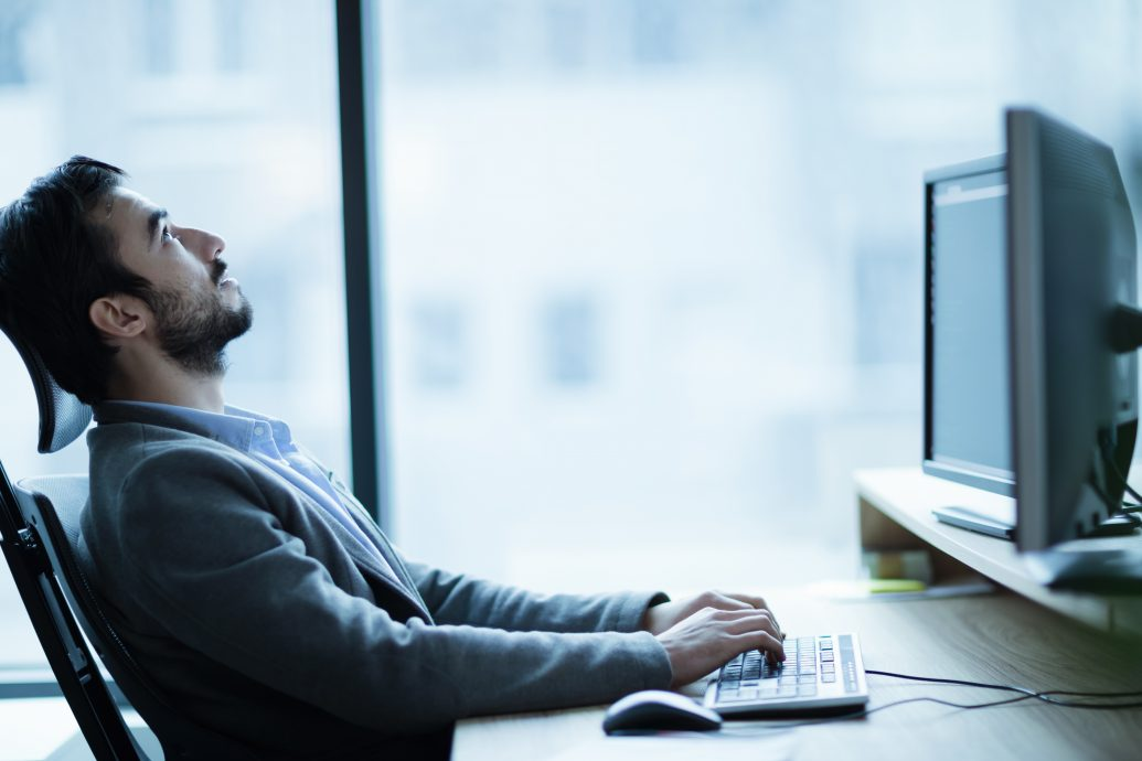 Overworked tired employee at workplace in office being unhappy